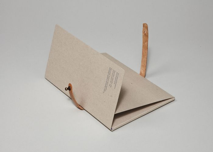 A set of postcards presented in a greyboard presentation folder with foil and embossing detail and secured with hand-made leather straps.