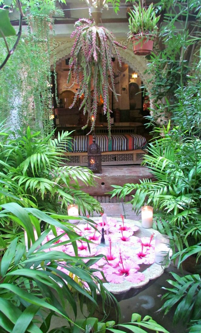 Carmen del Campillo - Casa Morisca, tetería. Fuente con flores rosa y velas. Carmen del Campillo - Moorish House, tearoom. Fountain with pink flowers and candles.