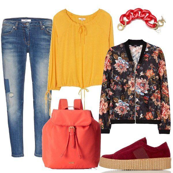 Outfit colorato, in caso di pioggia estiva, jeans con toppe, blusa solare con laccetti, leggerissimo bomber fiorato, sneakers di pelle rossa, zainetto e bracciale luminosi.