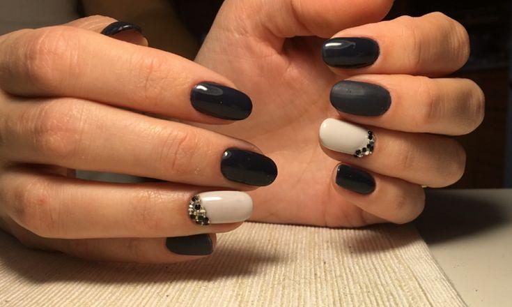 Decorazioni unghie di colore nero e bianco, brillantini sull'unghia del dito anulare