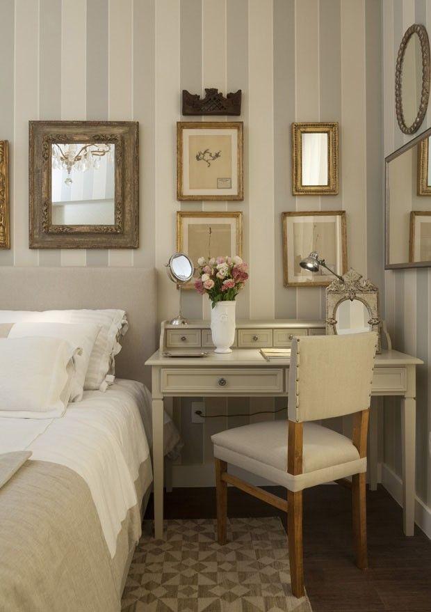 """""""Quarto clássico: [...] inspirado em uma mulher que esmera por detalhes e aprecia leitura em seus momentos de descanso. A tranquilidade é evocada nos tons de bege que cobrem desde os papéis de parede listrados à roupa de cama e o tapete. Para arrematar, um lustre do estilo francês e espelhos de molduras elaboradas.""""  Quartos e Etc (Foto: Divulgação)"""