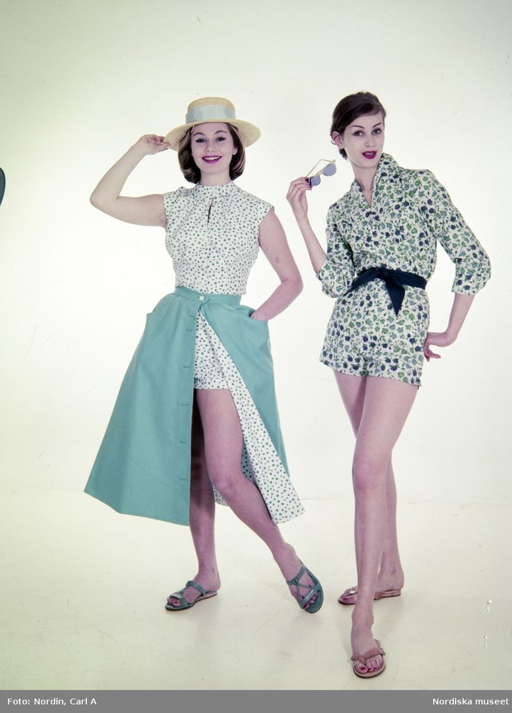 Sommarmode. Modell till vänster i prickig byxdress, turkos kjol, stråhatt och sandaler bredvid modell i blommig byxdress med blått midjeband, sandaler och solglasögon i handen. Fotograf: Carl A Nordin, 1960-1965