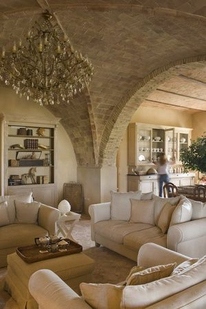 Tuscan warmth in cream tones for this lovely living space. Muted tones blend into a soothing setting. A simple interior with interesting sculptural lines in the walls/ceiling and light fixture.
