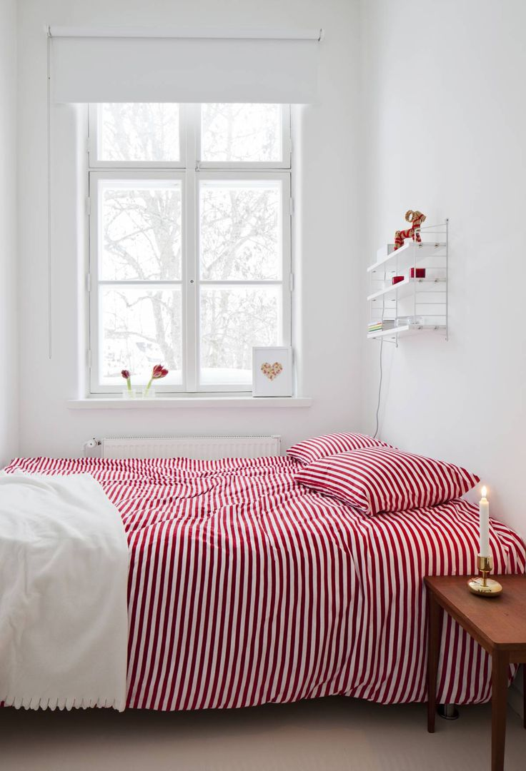 Marimekon punavalko-raidalliset lakanat tuovat jouluisen ilmeen makuu-huoneeseen. Iittalan Nappula-kynttilänjalka on Irinan itselleen ostama joululahja. String Pocket -hyllyn Irina sai äitienpäivälahjaksi Rikulta.