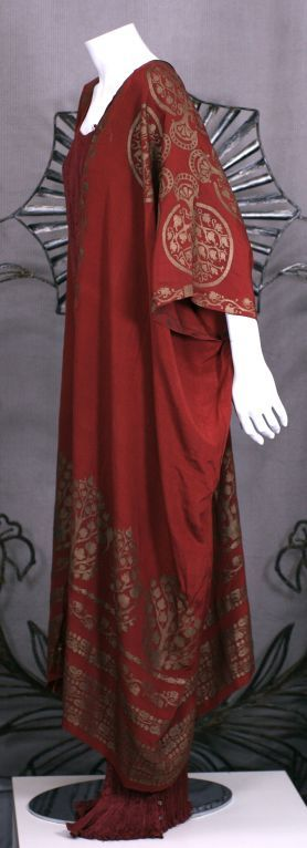 Mariano Fortuny Burgundy Stenciled Crepe Coat This ankle length silk crepe wrap, based on antique ethnic caftan styles, is cut square with openings for the arms. A stenciled Fortuny garment has minimal cuts so that the garment can serve as a canvas for the art work.