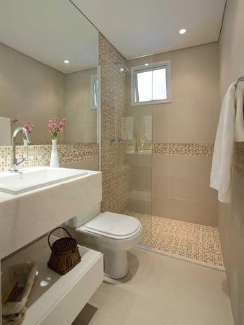 O banheiro claro conta com pastilhas para incrementar o visual. O vaso com flores dá um toque a mais. O projeto é das arquitetas Daniella e ...