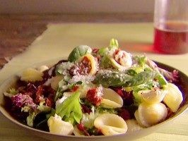 1 cup dried orecchiette pasta 2 cups Mediterranean-style mixed salad greens 2 TLBS sun-dried tomatoes (packed in olive oil), chopped 1 TLBS goat cheese or feta crumbled 2 TLBS grated Parmesan, plus garnish Cook,Drain pasta, reserving 1/2 cup of the water.  mix the salad greens with the sun-dried tomatoes, cheese, and Parmesan. Top with warm pasta and 1/2 cup of the reserved pasta water. Toss to combine and wilt the greens. Season pinch each of salt and pepper,Garnish with additional Parmesan