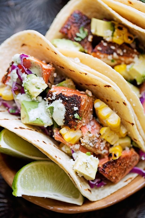 Simple blackened salmon tacos topped with avocados, corn, cotija cheese, and homemade jalapeño lime crema! These are the best fish tacos you'll ever have!