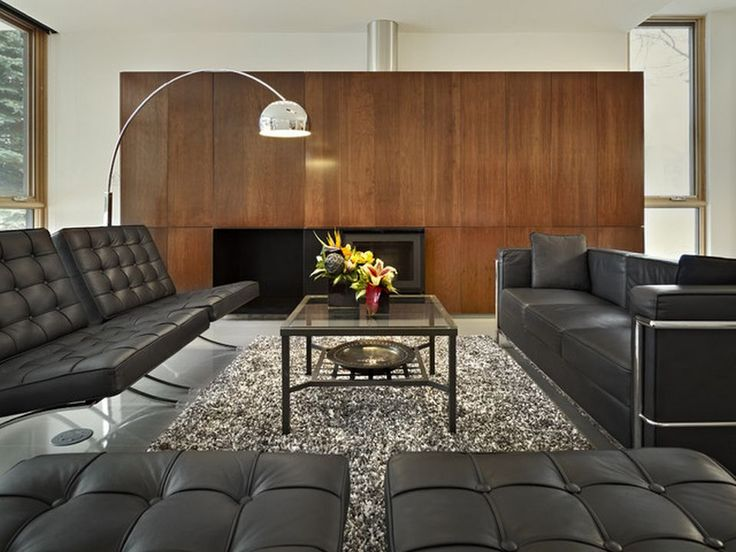 Modern And Luxurious Living Space With Elegant Rug Furnished With Best Black Sofas Set With Wooden Panel: Interesting Black Sofas Appearance In Eye-catching Living Room