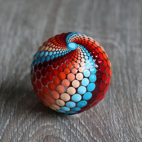 Mandala bal beschilderd met onder andere oranje, rode en blauwe acrylverf. De diameter van de bal is ongeveer 5 cm. De bal is gemaakt van helder glas en afgewerkt met glanzende vernis. Maar kan alsnog niet gebruikt worden voor buiten, etc. Op de vierde foto is als voorbeeld te zien hoe de mandala bal verpakt is in een organza zakje met een metalen ringetje (waar de bal opgeplaatst kan worden). Leuk om dus kado te geven! Bijvoorbeeld voor een huwelijk, housewarming, geboorte of yoga leraar…