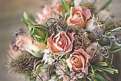 Jemná kombinácia bledých ruží a hnedých bodliačikov je spestrená zelenou rafiou.