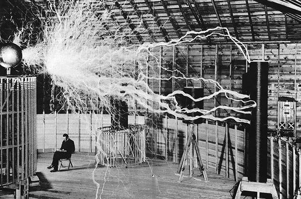 Nikola Tesla sedící ve své laboratoři pod svým transformátorem