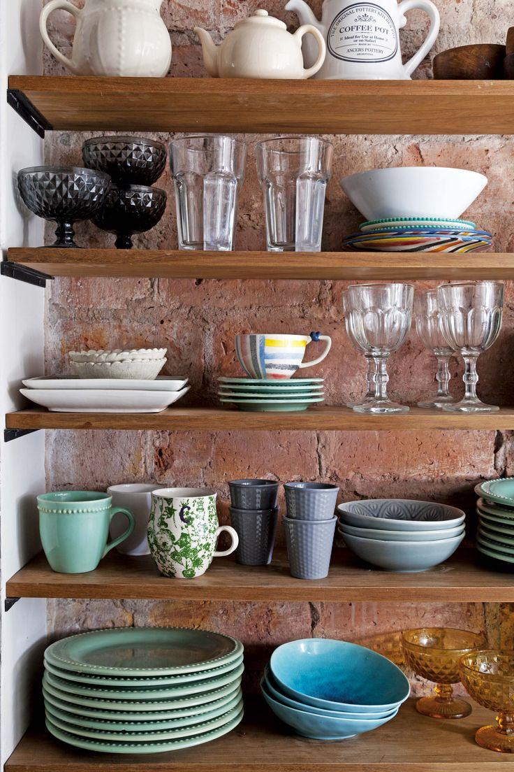 En esta cocina moderna, una pared divisoria de ladrillo se aprovechó con una estantería que suma espacio de guardado.