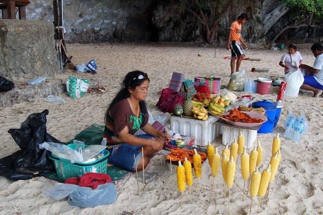 Ambulante vende panocchie arrosto, cosce di pollo e bibite sulla calda spiaggia di Railay - Krabi - Thailandia - Walking sells roasted corn, chicken legs and cold drinks on the hot Railay Beach - Krabi - Thailand
