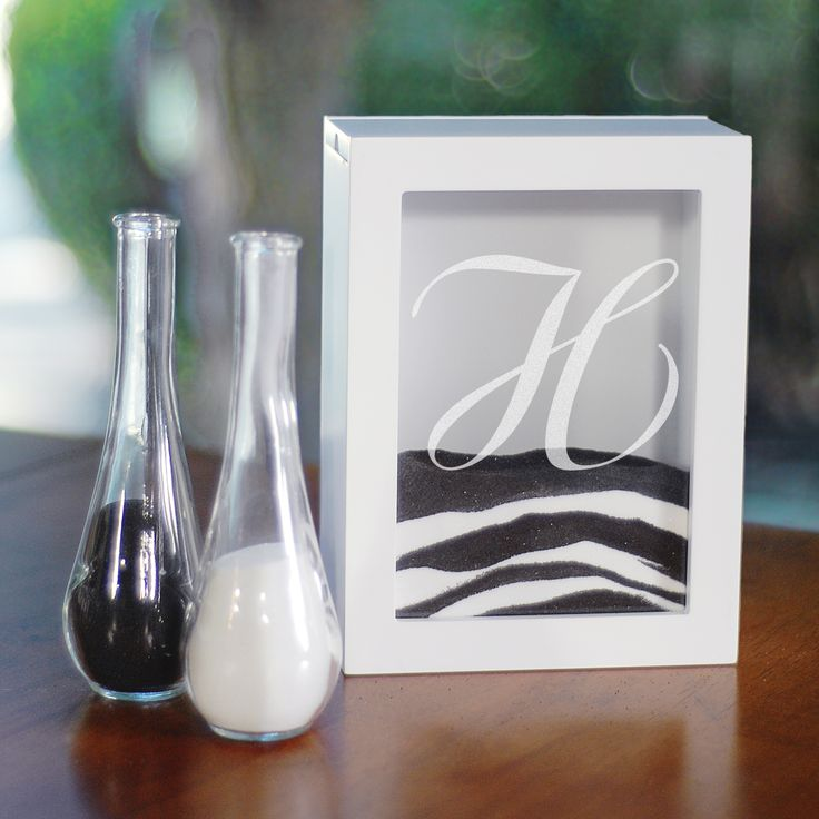 A trendy alternative for the unity candle, the White Unity Sand Ceremony Shadow Box Set comes complete with two vases, an easy-to-open shadow box and personalized glass insert. This beautiful box is the perfect way to remember your beautiful day.