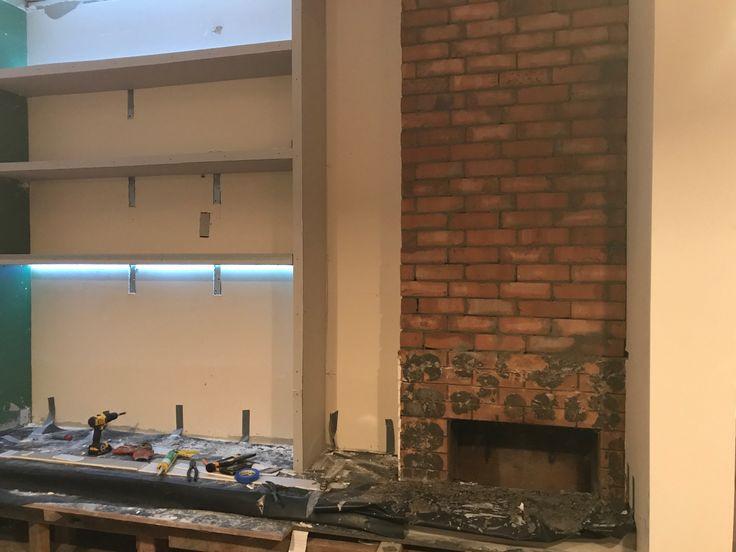 In progress...fireplace bricks in, strip lighting in, book shelves in...plaster awaits