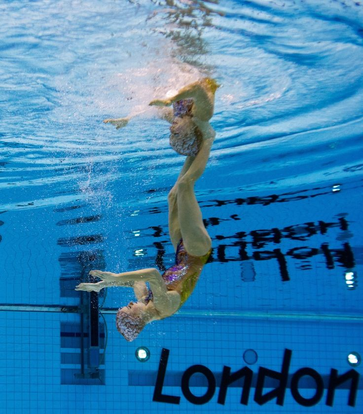 Foot-To-Shoulder PICTURE TAKEN WITH AN UNDERWATER CAMERA Brazil's Lara Teixeira and Brazil's Nayara Figueira compete in the duets free routine preliminary round during the synchronised swimming competition at the London 2012 Olympic Games