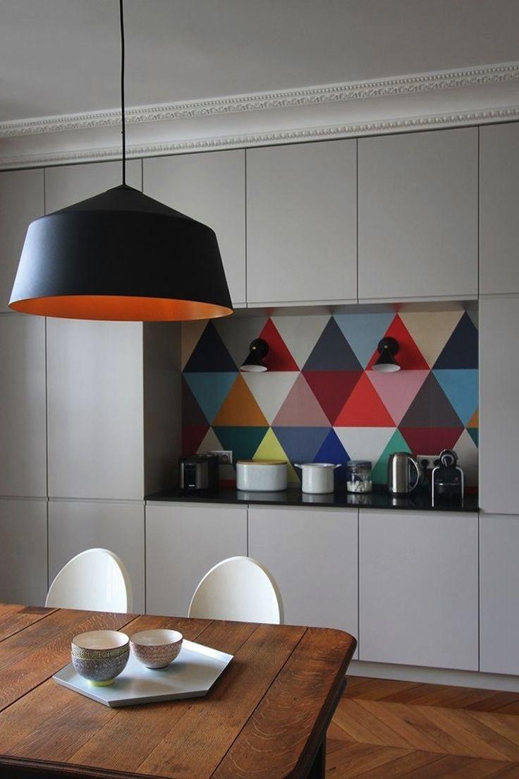 Массивная черная люстра от Camille Hermand висит над античным обеденным столом с белыми стульями в современном стиле. Фартук из разноцветной плитки поддерживает выбор именно такого светильника.