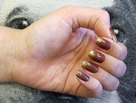 Unha marrom (esmalte Jaqueta, da Risque) com ombre de glitter dourado.
