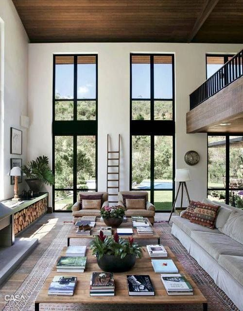 Wide and open modern rustic living room. Black and white are contrasted with a wood ceiling.
