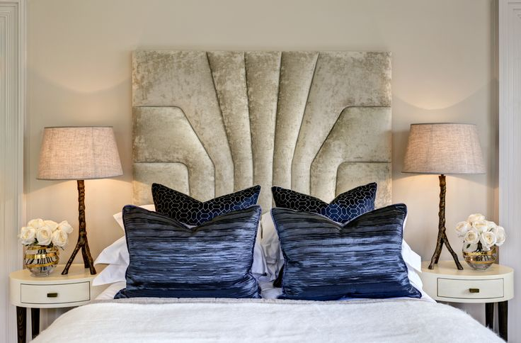 Guest bedroom with shaped upholstered headboard in grade II listed converted Georgian manor house designed with blue and gold accents by www.aji.co.uk