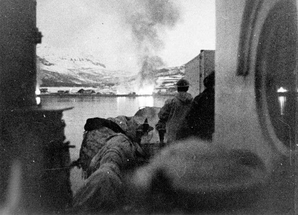 Shellbursts and fire on the shores of Bjerkvik at the head of the Herjangs Fjord, opposite Narvik, which was shelled by the Royal Navy, 5 June 1940.
