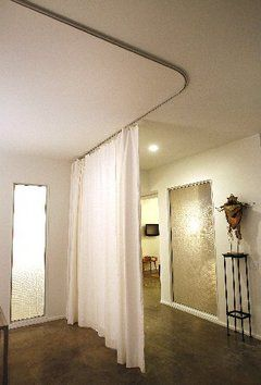 "curved ceiling track for ""hiding"" the office and separating it from the rest of the dining room."