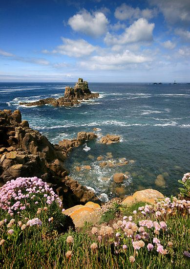 The rugged and rocky coastline of Lands End, Cornwall, UK looking out towards the lighthouse and rocks known as the Long Ships.