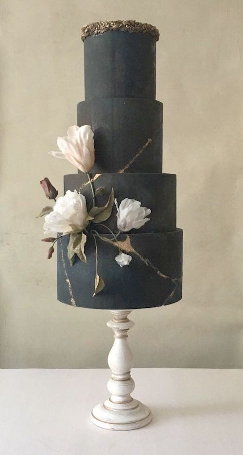 The subtle elegance of a black wedding cake crowned with gold leaves featuring an artsy flower detail