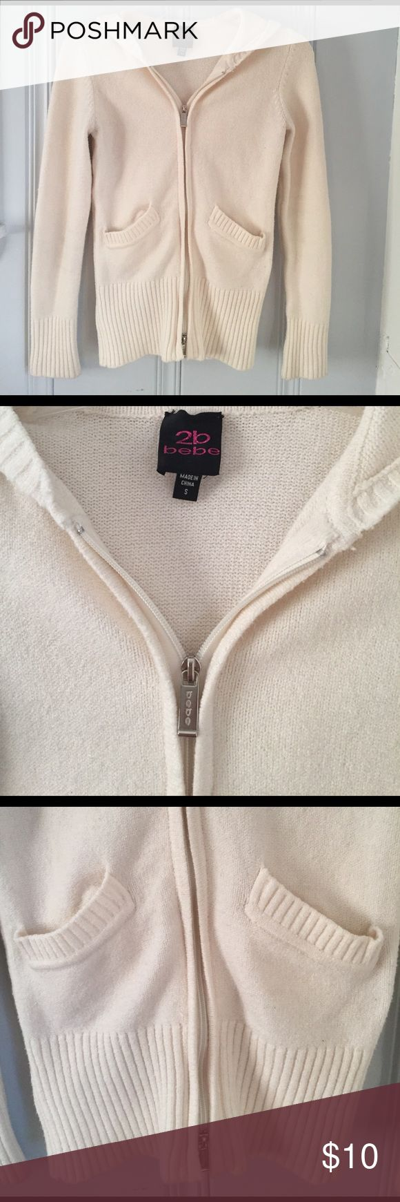 BEBE zip up hooded sweater Pre-loved cream colored BEBE zip up hooded sweater. Not sure the material but feels sort of like a knit only thicker bebe Tops Sweatshirts & Hoodies