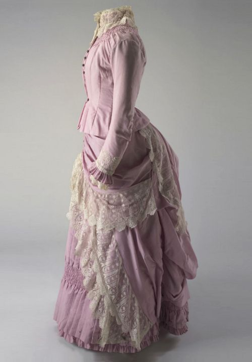 Pink wool bodice and skirt c. 1883 - 1886. Side view. This dress belonged to one of the daughters of William Pitt Faithfull, most likely his youngest daughter, Lilian.The tight fitting, boned bodice and bustled skirt decorated with lace flounces and frills are of the style fashionable among the middle and upper classes in Britain and Europe during this period.