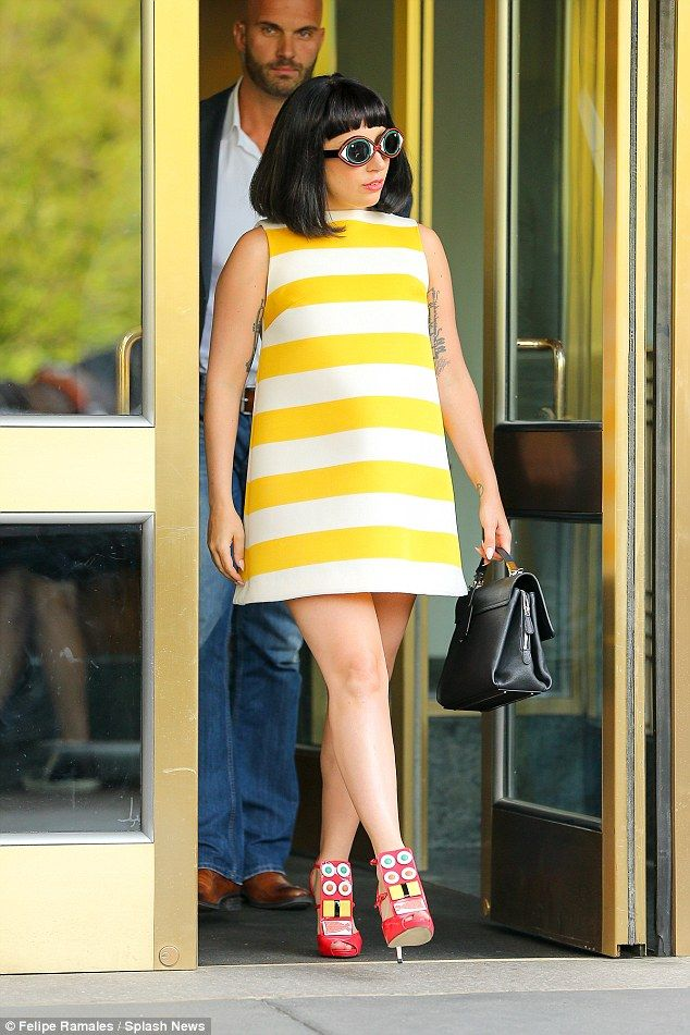 Bumble bee babe: She had on a Sixties inspired yellow and white striped mini dress with pi...