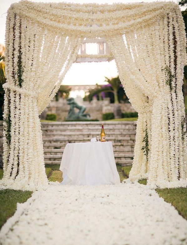 I love this idea of a canopy made from a curtain of flower. So pretty.