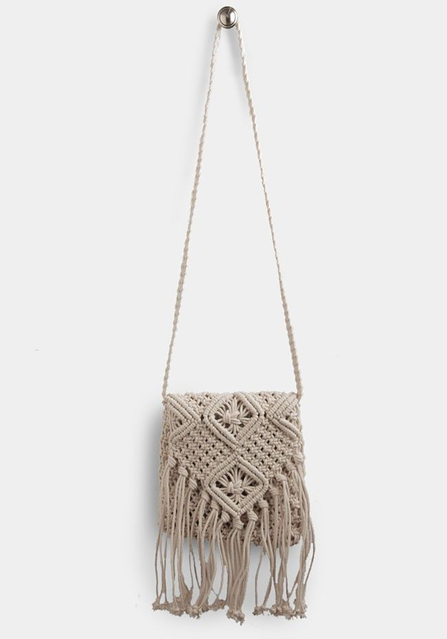 Cream-colored crossbody bag crafted in macrame crochet with fringe accents along the flap. Fully lined.
