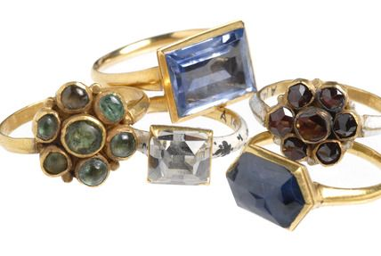 Selection of Cheapside Hoard rings: 16-17th century  Two flower shaped rings one originally set with 7 cabochon emeralds; the other is enamelled & set with garnets. The form of these two rings was inspired by Spanish fashions. Two gold finger rings set with a sapphire. Blue traditionally has a spiritual significance & symbolises purity; the sapphire is one of the stones used in ecclesiastical rings. And in the centre, gold finger ring set with a large table-cut diamond in enamelled gold…