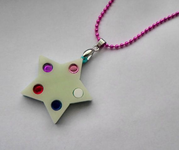 Based off of the gems secret room door in their home of the Crystal Temple, this necklace is modeled from the star lock on the door, adorned with the five gems.  This pendant is laser carved and cut out of a variety of reflective acrylics. Its mirror quality and shine captures light beautifully! You can choose from a cream star (show accurate) or a silver star (for added shine). Each star has a turquoise backing to match the color of the door.  You will receive one necklace connected with a…