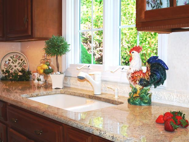 Elegant cream listello border tiles with a relief design topped with glistening polished mosaic marble create a lovely backsplash and beautifully complement the cream, taupe and black granite countertop. The