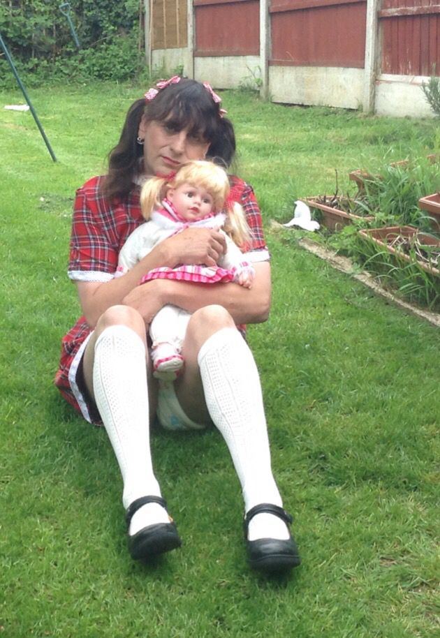 What a cute little pic of the little,girl wearing his cute little little girls dress the sissy is wearing little girls Mary Jane shoes white pelerine knee socks a little girls tartan dress with his hair in pigtails now don't worry sissy I'm sure no one is going to see you're wearing a nappy