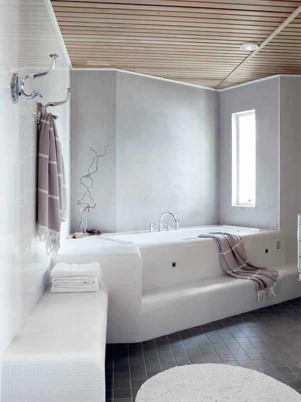 Kylpyhuoneessa on tilaa useammallekin peseytyjälle. Suihkuja on kaksi, ja saunaan mahtuu kahdeksan henkeä. Poreammeessa on mukava rentoutua. Kaikki laatat ovat Laattapisteestä. Ammeen taustaseinä sekä suihkutilan päätyseinät on käsitelty kosteisiin tiloihin tarkoitetulla Decosin sisustuslaastilla. | Järven lumoamat | Koti ja keittiö