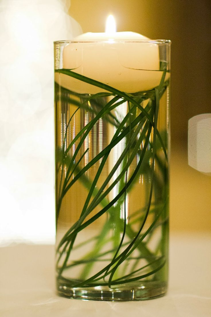 simple glass cylinders with submerged bear grass and a floating candle  u2026
