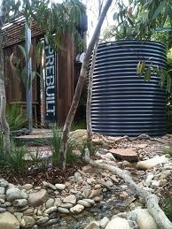 Australian native garden -  rocks, trees, grass plants and water tank (no water is wasted in Australia)