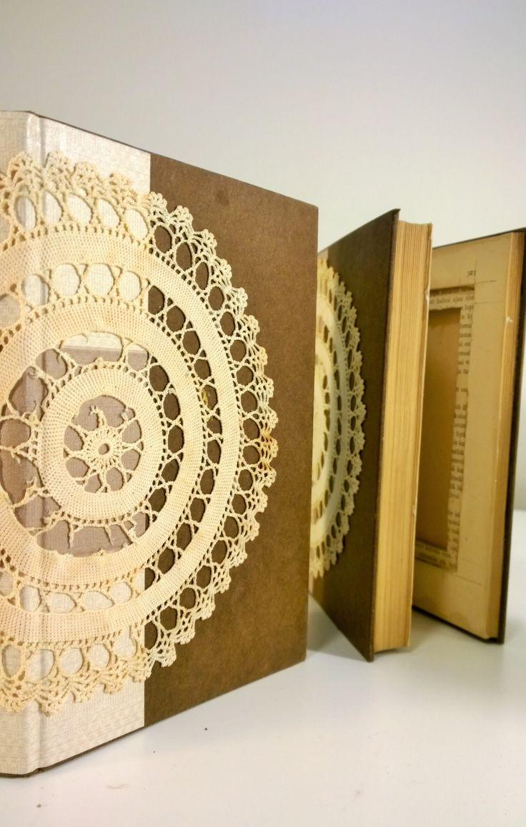 Vanhojen kirjojen kannet koristeltu tapetilla ja pitsillä. Sisäsivut kaiverrettu kuvia varten.