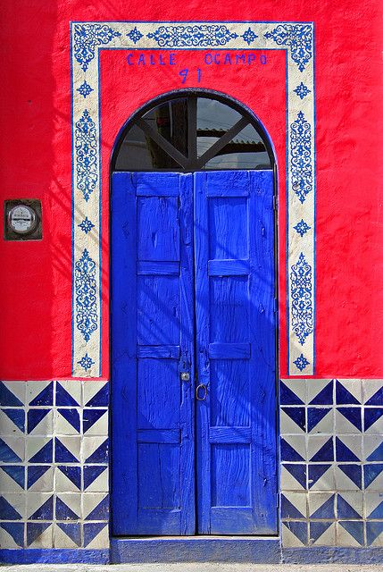 Love the bright, colorful paint and blue and white chevron tile around this blue door in Mexico.