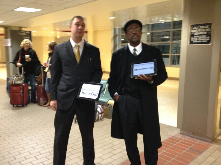 At the airport - Two chauffeurs look for their passengers. You can see these 50 feet away.