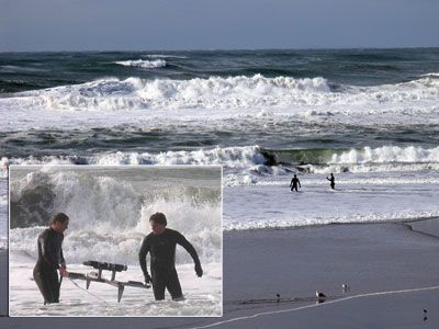 Andrew Schwartz and Dan Hanes maneuver an Aquadopp current profiler and its frame in the surf.