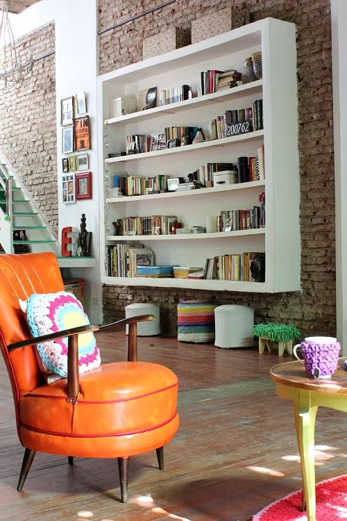 Eclectic vintage loft living space. Orange leather chair, exposed brick and expansive shelving.