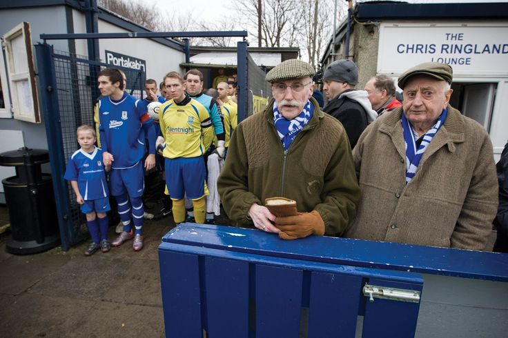 Glossop North End 0 Barnoldswick Town 1, 19/02/2011. Surrey Street, North West Counties League Premier Division. Two elderly Glossop North End supporters waiting for the teams to come out  before their club's game with Barnoldswick Town (in yellow) in the Vodkat North West Counties League premier division at the Surrey Street ground. The visitors won the match by one goal to nil watched by a crowd of 203 spectators. Glossop North End celebrated their 125th anniversary in 2011 and were once…
