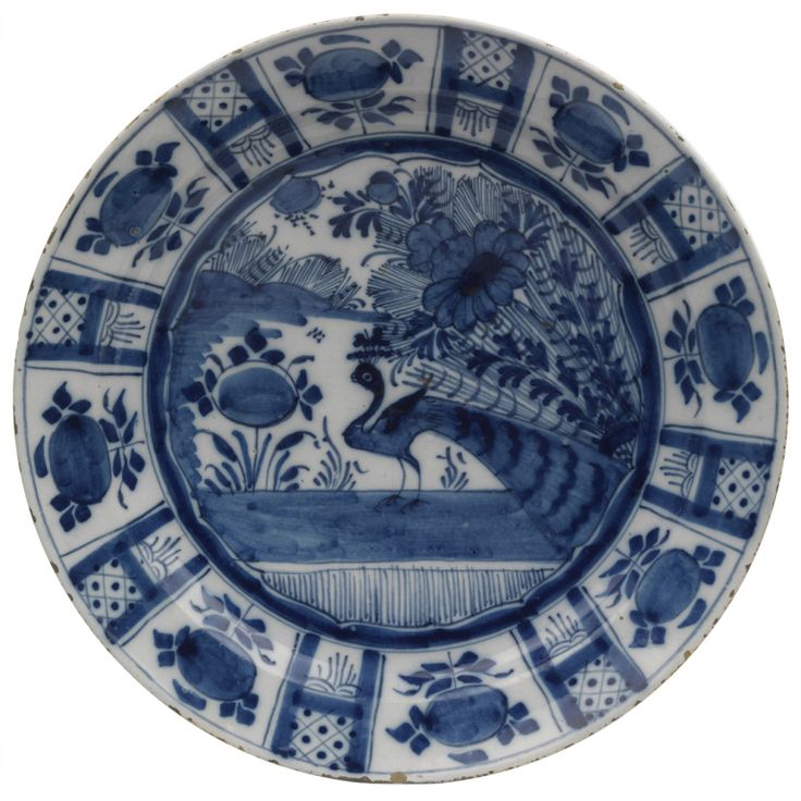 Dutch Delft Charger, Holland: A charming Dutch Delft 18th century blue and white charger in the Chinese Wanli style, with a large peacock in the central panel.
