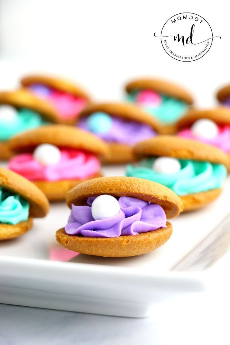 Clam Shell Cookies are a delicious and quick way to create the perfect dessert for an under the sea or mermaid party. Buttercream frosting and pearls!