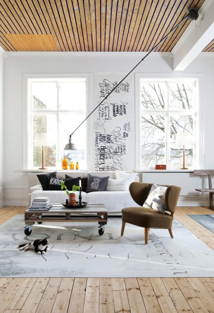 VAKRE ORD: Mellom to av vinduene i stuen har beboer lekt seg med ulike fonter på veggen. Lampen er en Triplex, teppet fra Ylva Skarp.
